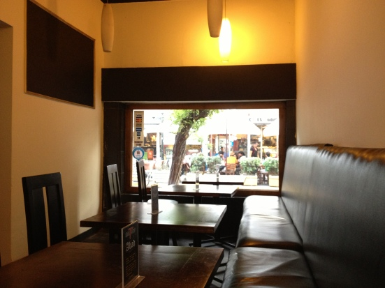 Vista desde la misma mesa hacia un ventanal que da a la calle