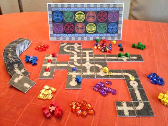 Una muestra ilustrada del los componentes del juego en su conjunto; las gemas son cuentas de bisutería en acrílico de diferentes colores